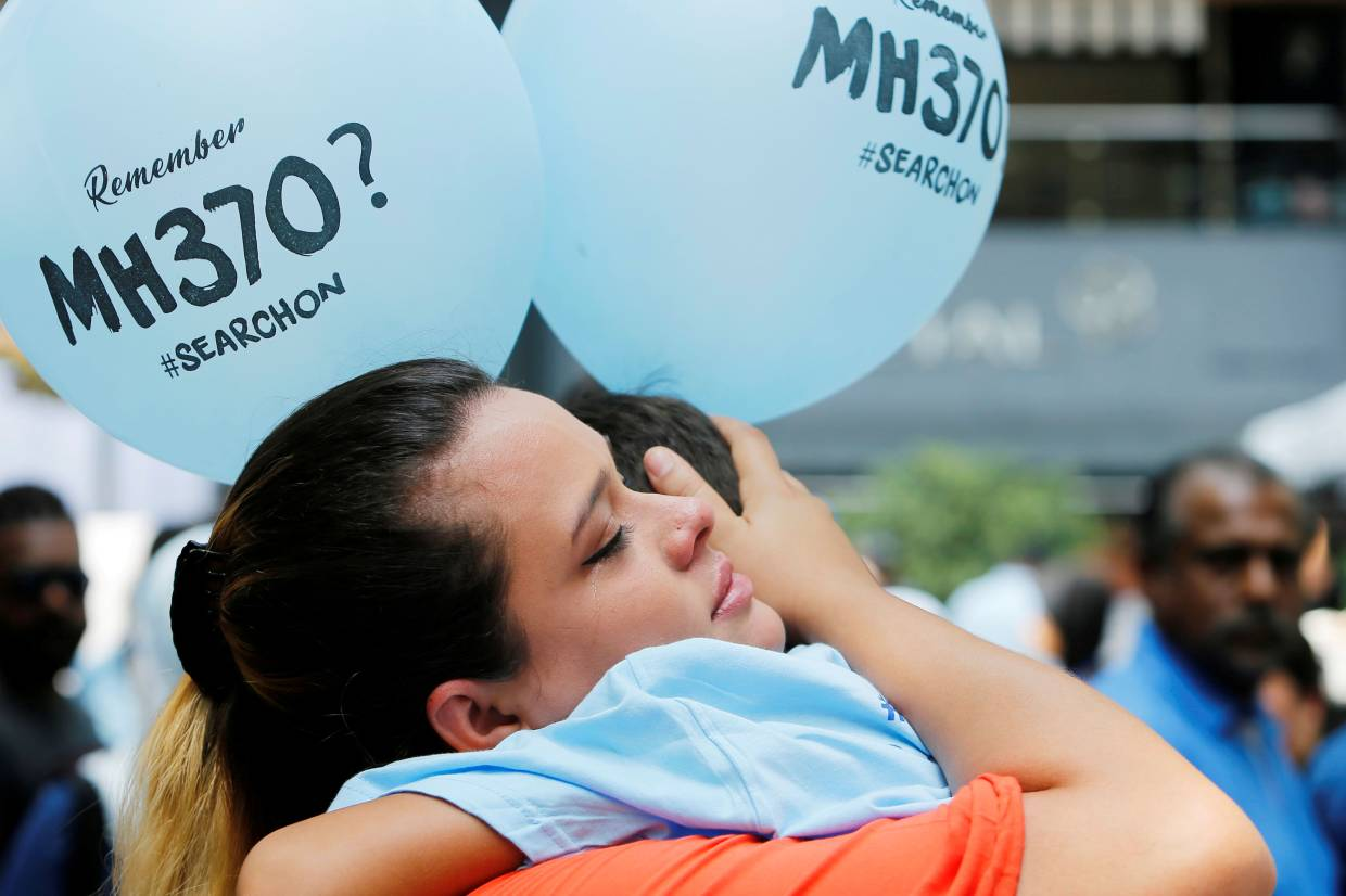 FILE PHOTO: Michelle Gomes, daughter of Patrick Gomes who was the in-flight supervisor onboard the missing Malaysia Airlines flight MH370, comforts her son Rafael Gomes during its fifth annual remembrance event in Kuala Lumpur
